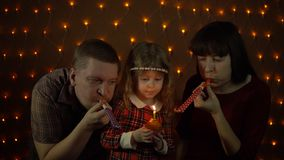 Family together celebrate the holiday. A little sweet girl blows out a candle on the muffin, her parents are playing in colorful party horns. Family together stock video