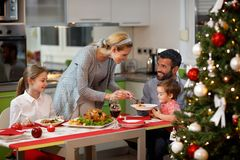 Family together at decorated table having festively dinner Royalty Free Stock Photo