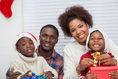 Family together doing gifts and smiling Stock Photos
