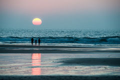 Family together walking on the beach at sunset. Stock Image