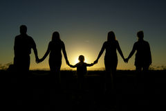 Family Togetherness and unity in Sunset. A family holding hands in a show of unity and togetherness silhouetted in the sunset Stock Photo