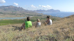 The family at the top of the hill looks at the lake in the valley, on the sea, on the mountains, on the plain with stock video footage