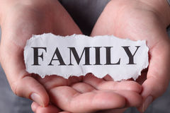 Family. Torn piece of paper with the word Family in the woman's palms. Close-up Royalty Free Stock Images