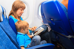 Family with touch pad in plane. Mother and son with touch pad in plane, family travel Royalty Free Stock Image