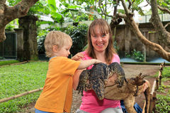 Family touching monitor lizard Royalty Free Stock Images