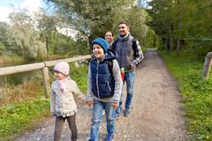 Family with backpacks hiking or walking in woods stock images