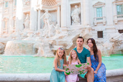Family with touristic map near Fontana di Trevi, Rome, Italy. Happy father and kids enjoy italian vacation holiday in Stock Photography