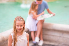 Family with touristic map near Fontana di Trevi, Rome, Italy. Portrait of little girl background of Trevi Fountain. Royalty Free Stock Images
