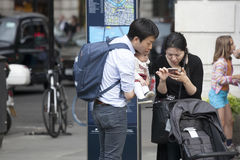 Family of tourists: father, mother and baby in her arms - looking in the phone, trying to determine the route Stock Image