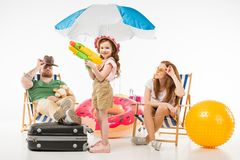 Family of tourists with sun loungers, sunshade, flotation ring and water gun stock photo