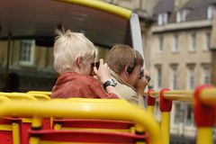 Family tourists taking pictures. Father and son taking photos from an open top bus, during a tour of the city (Bath royalty free stock images