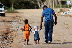 Family in Township. On Saturday, 19 March 2011, a father and his two little girls walked home as the sun started to set in a township in Addo, South Africa stock image