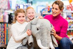 Family in toy store cuddling with stuffed animal Stock Image