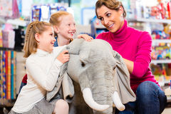 Family in toy store cuddling with stuffed animal Stock Photo