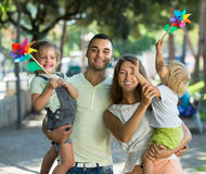 Family with toy windmills at park Royalty Free Stock Image