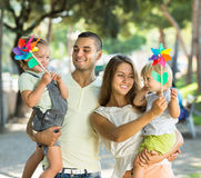 Family with toy windmills at park Royalty Free Stock Images
