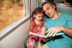 Family on the train reading a book Royalty Free Stock Images