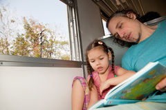 Family on the train reading a book Stock Photo