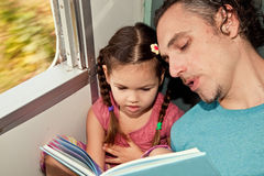 Family on the train reading a book Stock Images