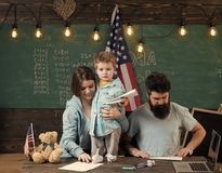 Family training. American family at desk with son making paper planes. Kid with parents in classroom with usa flag. Chalkboard on background. Parents teaching Stock Photo