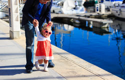 Family travel- father and little daughter learning to walk in port Stock Photography