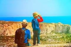 Family travel -father and son hiking with backpack in mountains. Family travel -father and little son hiking with backpack in mountains royalty free stock images