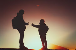 Family travel- father and son with backpacks hiking at sunset Royalty Free Stock Photography