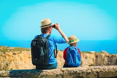 Family travel -father and son hiking with backpack in mountains. Family travel -father and little son hiking with backpack in mountains royalty free stock photo