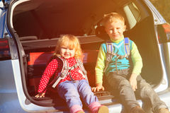 Family travel - little boy and toddler girl with luggage in the car. Family car travel - happy little boy and toddler girl with luggage in the car Stock Image