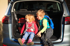 Family travel - little boy and toddler girl with luggage in the car. Ready to travel Royalty Free Stock Images