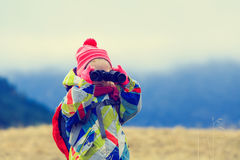 Family travel- little girl with binoculars exploring winter mountains. Family travel- cute little girl with binoculars exploring winter mountains Royalty Free Stock Images