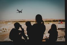 Family travel- mother with kids looking at planes in airport. Family travel- mother with three kids looking at planes in airport royalty free stock image