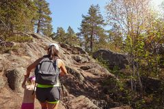 Family travel. Strong mother helps her daughter climbing stock photography