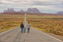 Family travel to Monument Valley and holding hands. Family travel and walking down road to Monument Valley while holding hands with a child Royalty Free Stock Image