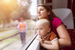 Family travel in train. Mother with son in her lap traveling in train Stock Photo