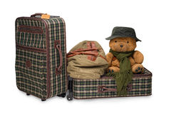 Family Travel. Two suitcases, a handbag and a teddy bear with hat. Isolated Royalty Free Stock Image