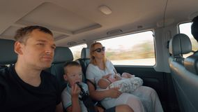 Family traveling by car. Family of parents and two children traveling by car. Mom, dad and son looking at the road, baby girl sleeping stock video