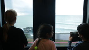 Family traveling on a train and looks through the window at the sea stock video footage