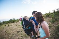 The family travels with the child. A man carries his son in a backpack. Walk with the family. The boy is traveling with his stock photos