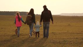 Family travels with the dog on the plain. teamwork of a close-knit family. mother, little child and daughters and pets. Family travels with the dog on plain stock video