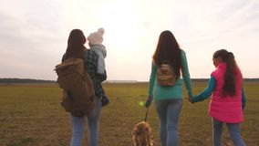Family travels with the dog on the plain. Teamwork of a close-knit family. Mother, little child and daughters and pets. Family travels with the dog on plain stock footage