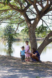 Family with tree near lagoon Royalty Free Stock Images
