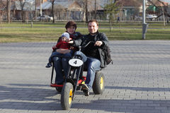 Family on tricycle. Family on the tricycle at a park in spring royalty free stock photos