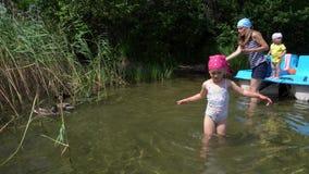 Family trip with catamaran stop on desert island. Girl wade water. Gimbal motion stock video