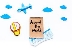 Family trip concept. Airplan toy, air balloon cookie, airplan tickets. Around the world hand lettering in notebook on. White background top view Stock Images