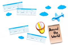 Family trip concept. Airplan toy, air balloon cookie, airplan tickets. Around the world hand lettering in notebook on. White background top view Royalty Free Stock Photography