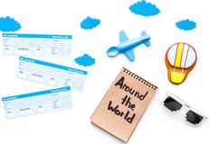 Family trip concept. Airplan toy, air balloon cookie, airplan tickets. Around the world hand lettering in notebook on. White background top view Royalty Free Stock Photos