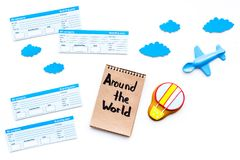 Family trip concept. Airplan toy, air balloon cookie, airplan tickets. Around the world hand lettering in notebook on. White background top view Royalty Free Stock Images