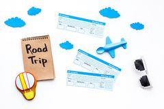Family trip concept. Airplan toy, air balloon cookie, airplan tickets. Road trip hand lettering in notebook on white. Background top view Stock Photos