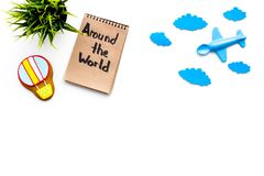 Family trip concept. Airplan toy, air balloon cookie. Around the world hand lettering in notebook on white background. Top view Stock Images
